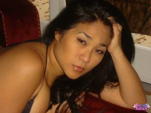 Chubby Asian girl with ebony hair poses non bare in a ebony swimsuit
