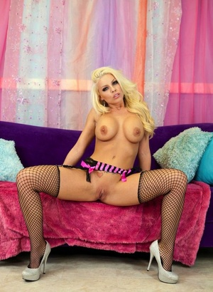 Blonde solo girl Britney Amber shows her big tits and twat in mesh nylons