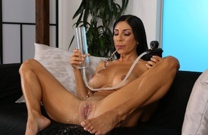 Busty black haired Rachel Evans pissing all over and toying her horny twat