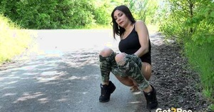 Brunette chick pulls down ripped camo pants to piss on side road