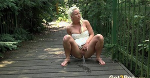 Natural blonde Lickylex squats on a wooden bridge to take a pee