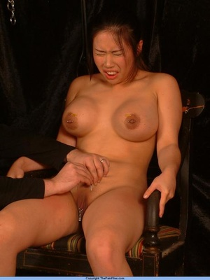 Naked Asian girl with big boobs has clamps fastened to vagina before needle play