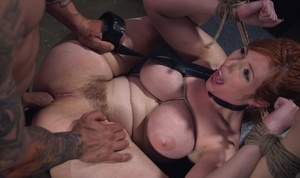 Buxomy redhead Lauren Phillips is gagged and tied up with rope for a hard fuck
