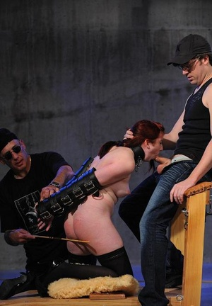 Redhead female is made to suck a cock while being caned simultaneously