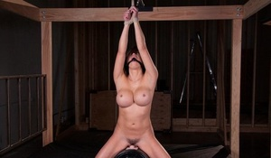 Busty and ball-gagged Asian Mia Lelani rides a Sybian with hands tied over her head