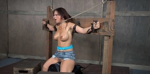 Busty chick Syren De Mer is restrained in place and made to gargle cock