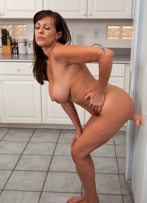 Aged lady exposing nice melons in kitchen before masturbating with sex toy