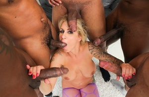 Tattooed blonde with big tits sucks multiple BBCs in molten interracial gangbang
