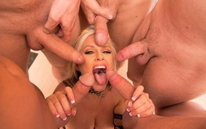 Hot blonde female Alena Croft is surrounded by big schlongs to suck on