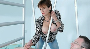 Busty mature fetish lady in blue jeans stroking off a big cock