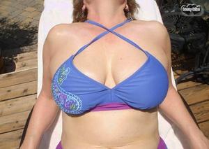 Sexy mature lady Busty Bliss sets her natural bra-stuffers free of bikini top