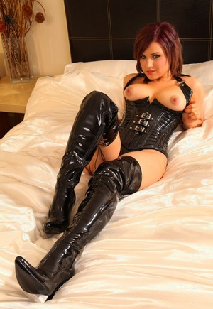 Bare titted Jocelyn-Kay in spandex bustier & high heel boots plays with her crop