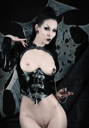Fetish model Razor Candi attaches nipple clamps attired in latex clothing