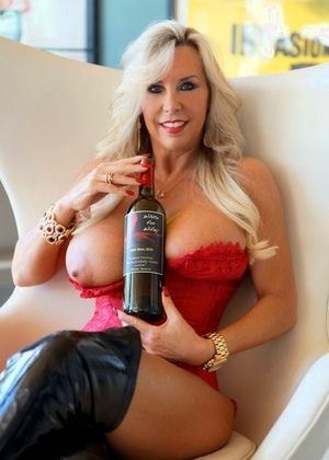 Platinum-blonde housewife extracts her huge tits from crimson lingerie in stripper boots