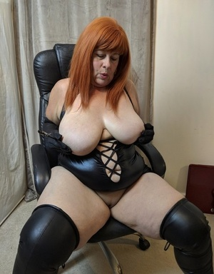 Older redhead Mrs Leather slaps her bald cooter with crop in latex attire