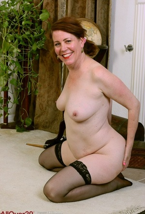 Mature lady Caitlin Moore removes maid uniform to model bare in stockings