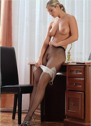 Beautiful female takes off her taut dress before removing stockings