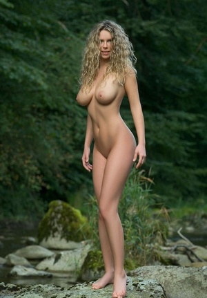 Leggy solo girl with long curly hair models naked among rocks in the river