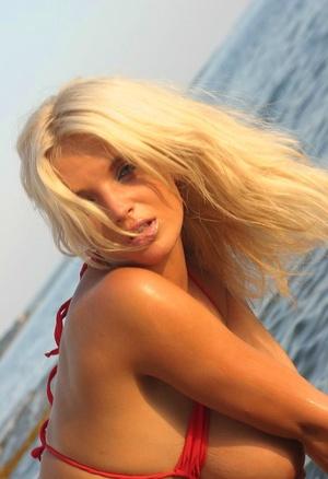 Hot blonde Ines Cudna unleashes her huge tits from bikini alongside a seawall