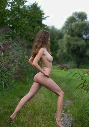 White solo girl Susann displays her big boobs while posing bare in backyard