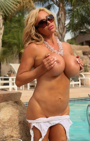 Towheaded bombshell Rachel Aziani releases her large melons from wet swimsuit
