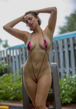 Beautiful woman in booty shorts and bikini getting bare to show saggy jugs poolside