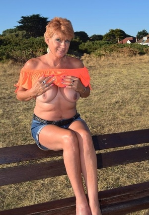 Mature redhead Dimonty shows her tits on a bench in a country realm