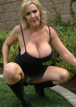 Mature blonde woman takes off her boots and lets out her huge boobs