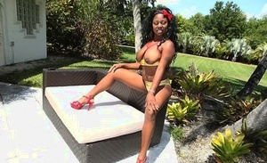 Ebony solo model Leslie oils up her fat boobs and ass out on the patio