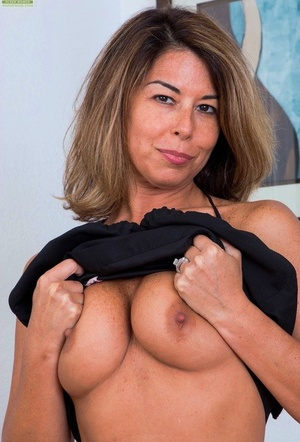 Mature housewife Niki May takes a sip of wine before showing her pink snatch
